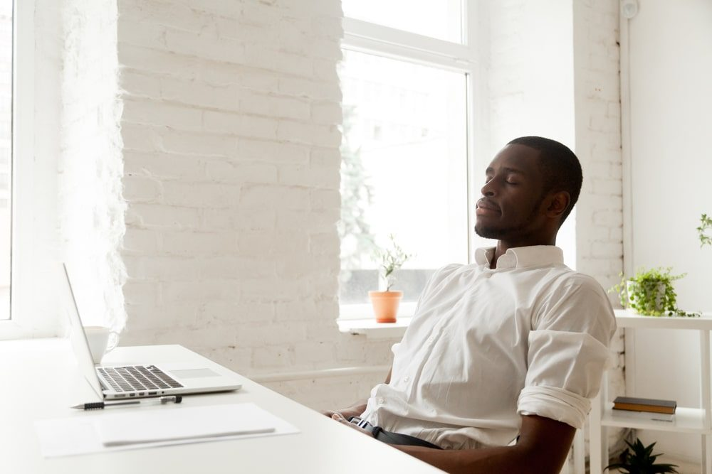 Man breathing at his desk to relax