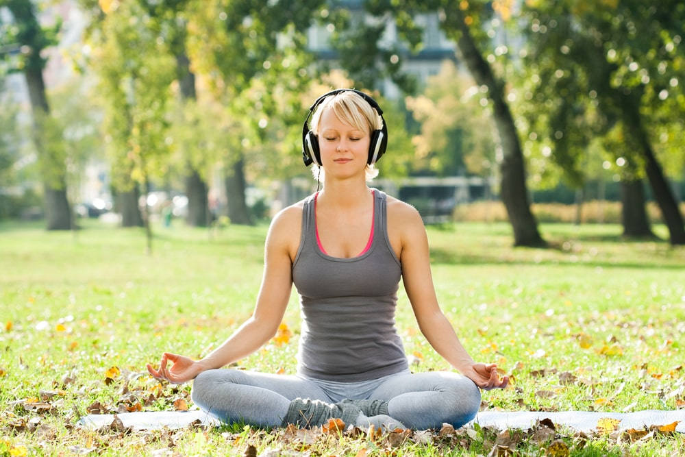 Woman meditating at a park with headphones on