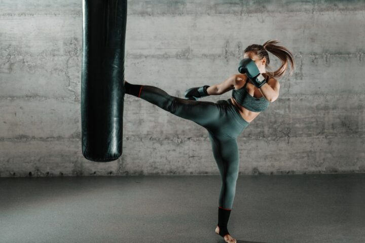 Woman practicing mixed martial arts on a heavy bag